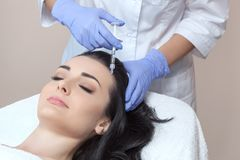 The doctor cosmetologist makes the procedure of mesotherapy in woman`s head. Procedure of mesotherapy. The doctor cosmetologist makes the procedure of Stock Photos