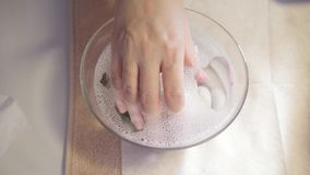 Procedure moisturizing nail, hand lay in the bath with water. Close-up. Manicure beauty salon. manicurist makes the stock footage