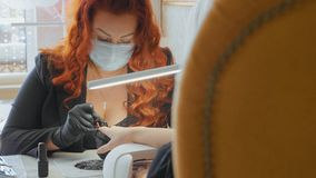 The procedure of painting nails. Manicure procedure in the beauty salon. royalty free stock photos