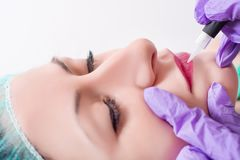 Procedure of professional applying permanent makeup on woman lips stock images