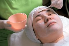The procedure of rejuvenation and cleansing of the skin in the cosmetology center. Spa treatment for a young woman receiving a royalty free stock image