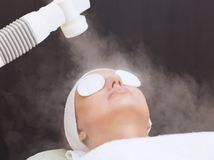 The procedure of steaming the skin of the face of a young woman. Before cleaning the skin in a cosmetology salon royalty free stock photos