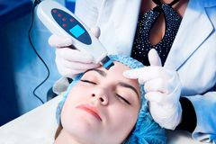 Procedure of ultrasonic cleaning of face. Ultrasonic scrubber.Medical treatment and skin care. Procedure of ultrasonic cleaning of face. Medical treatment and royalty free stock photos