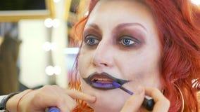 Proces die Halloween-make-up op gezicht toepassen de vrouw in verpleegstersstijl Stock Foto