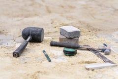 Proces kłaść bruk przy jardem Kamienie kłaść na piasku tła zbliżenie praca metal śrubuje biały narzędzie pracę Zdjęcia Royalty Free