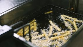 Proces om frieten in de frituurpan in 4k resolutie in langzame motie te koken stock footage