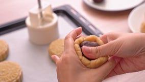 Proces om maancake voor de medio-Herfstfestival te maken - Verpakkend rood boondeeg die met gebakjedeeg vullen Vrouwen feestelijk stock video