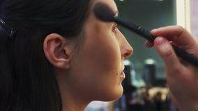 Proces om make-up te maken, Grimeur die met borstel aan modelgezicht werken stock video