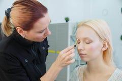Proces om make-up te maken Grimeur die met borstel aan modelgezicht werken royalty-vrije stock afbeeldingen