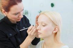 Proces om make-up te maken Grimeur die met borstel aan modelgezicht werken royalty-vrije stock foto's