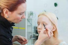 Proces om make-up te maken Grimeur die met borstel aan modelgezicht werken royalty-vrije stock foto