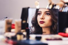 Proces om make-up te maken het gezicht van model wordt weerspiegeld in spiegel tijdens samenstelling royalty-vrije stock afbeelding