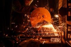 Proces om metaalbuizen op de machine te snijden De vonken vliegen in verschillende richtingen in dark Stock Afbeelding