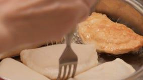 Proces om te koken cheburek Kaukasisch en oostelijk voedsel Het meisje draait de pastei op een glanzende pan met twee vorken stock video