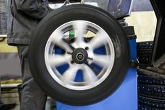 Proces równoważenie i dopasowanie samochodowa opona toczy wewnątrz ruch, auto remontowa usługa, garaż Obrazy Stock