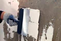 Proces stosować białego kit na betonowej szarości ścianie Zdjęcia Royalty Free