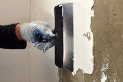 Proces stosować białego kit na betonowej szarości ścianie Fotografia Royalty Free