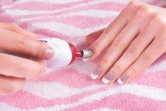 Proces usuwa starego gel od gwoździ z ostrzarza narzędziem na różowym tle obraz royalty free