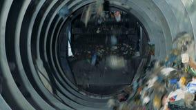 Proces van het mechanische huisvuil sorteren Afvaldalingen van een transportband in een roterende machine om te sorteren stock video