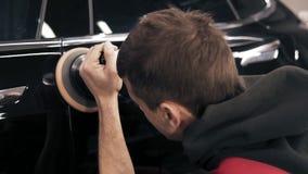 Proces van het nauwkeurige oppoetsen van een zwarte nieuwe auto stock videobeelden