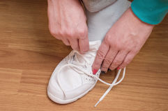 Proces van kleding van witte sportentennisschoenen Royalty-vrije Stock Afbeeldingen