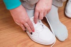 Proces van kleding van witte sportentennisschoenen Royalty-vrije Stock Fotografie