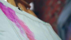 Proces van tekening De kunstenaar schildert een borstel op canvas van denim stock footage