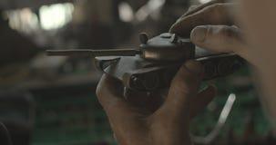 Proces van verwezenlijking van stuk speelgoed ijzertank De onbekende man inspacting het in zijn workshop ROOD cameraschot royalty-vrije stock foto's