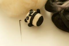Proces van viltbekleding een stuk speelgoed panda van een witte en zwarte wol Stock Afbeeldingen