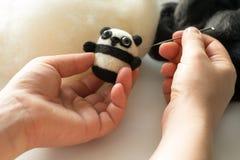 Proces van viltbekleding een stuk speelgoed panda van een witte en zwarte wol Royalty-vrije Stock Foto's
