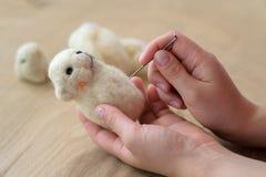 Proces van viltbekleding een stuk speelgoed van een lichte wol op een houten achtergrond Stock Foto's