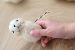 Proces van viltbekleding een stuk speelgoed van een lichte wol op een houten achtergrond Royalty-vrije Stock Foto