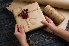 Proces zawijający w rzemiosło papierze pakunku prezent, wiązany z smyczkową i kleiącą wosk foką na drewnianym czarnym tle zdjęcia royalty free