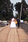 Procesión de la boda en un puente de madera Imágenes de archivo libres de regalías