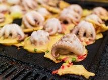 Proceso a cocinar el takoyaki, pulpo asado a la parrilla en bola cremosa foto de archivo