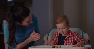 Proceso de aprendizaje de la madre que intenta enseñar a su niño a contar con los fingeres usando juegos metrajes