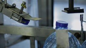Proceso de cerrar las botellas plásticas con agua en compañía almacen de video