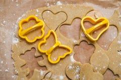 Proceso de cortar el pan de jengibre en la forma de corazones, de mariposas y de flores foto de archivo
