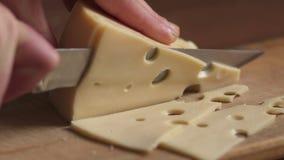 Proceso de cortar el queso en un primer de la tabla de cortar, cámara lenta metrajes
