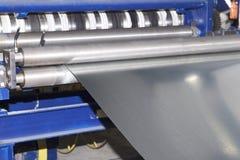 Proceso de cortar una hoja ancha del metal en tiras estrechas en una máquina imagenes de archivo