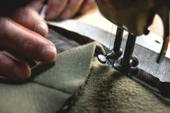 Proceso de costura de la correa de cuero las manos del viejo hombre detrás de la costura Taller de cuero costura del vintage de l imagenes de archivo
