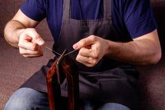 proceso de cuero de la adaptación del arte - las manos de los hombres que cosen la cartera marrón foto de archivo