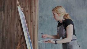 Proceso de dibujo: pintor de sexo femenino rubio experto talentoso crear imagen abstracta moderna con las pinturas acrílicas en l