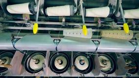 Proceso de enrrollamiento de coser los carretes realizado en la máquina industrial en una fábrica de la materia textil metrajes