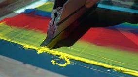 Proceso de impresión colorido de la pantalla de seda en la camiseta metrajes
