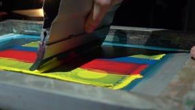 Proceso de impresión colorido de la pantalla de seda en la camiseta almacen de metraje de vídeo
