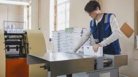 Proceso de impresión - el trabajador inserta las hojas de papel en prensa industrial fotografía de archivo libre de regalías