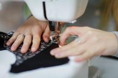 Proceso de la adaptación - manos del ` s de las mujeres detrás de su costura Fotografía de archivo
