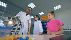 Proceso de la demostración de un robot del juguete a los niños realizado por un profesional del varón almacen de video