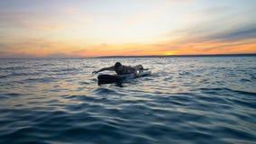 Proceso de la natación de una señora atractiva mientras que miente en un paddleboard Concepto de la libertad metrajes
